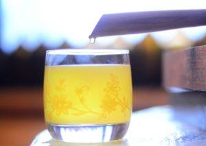 Масло капает в стакан из бочки