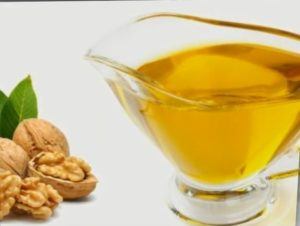 Три грецких ореха и чашка с маслом